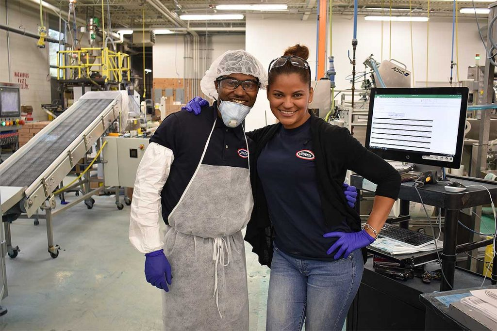 Urnex Factory Employees Smiling And Posing For A Photo