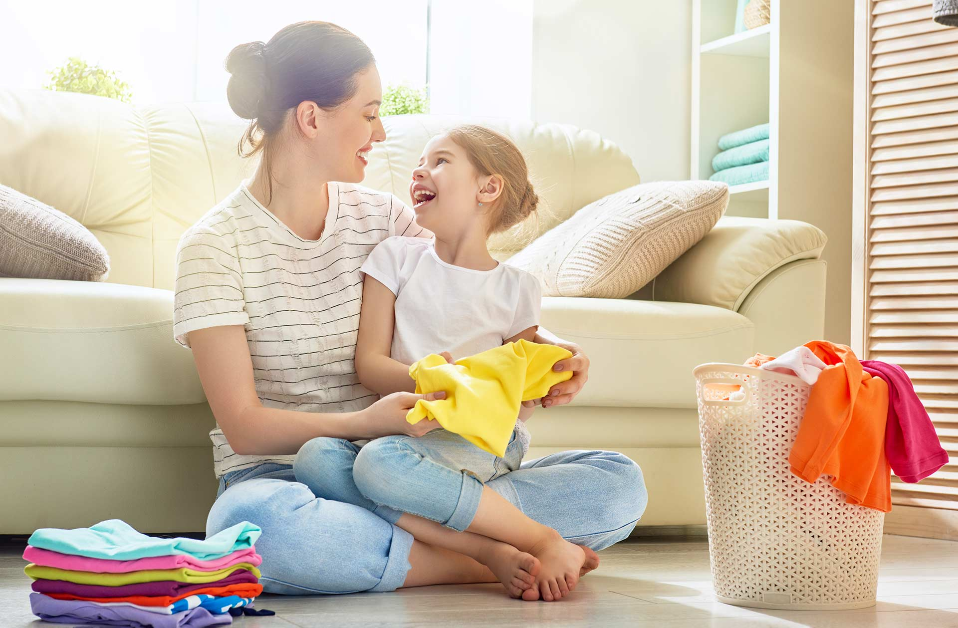 A woman and her young daughter happily fold laundry together