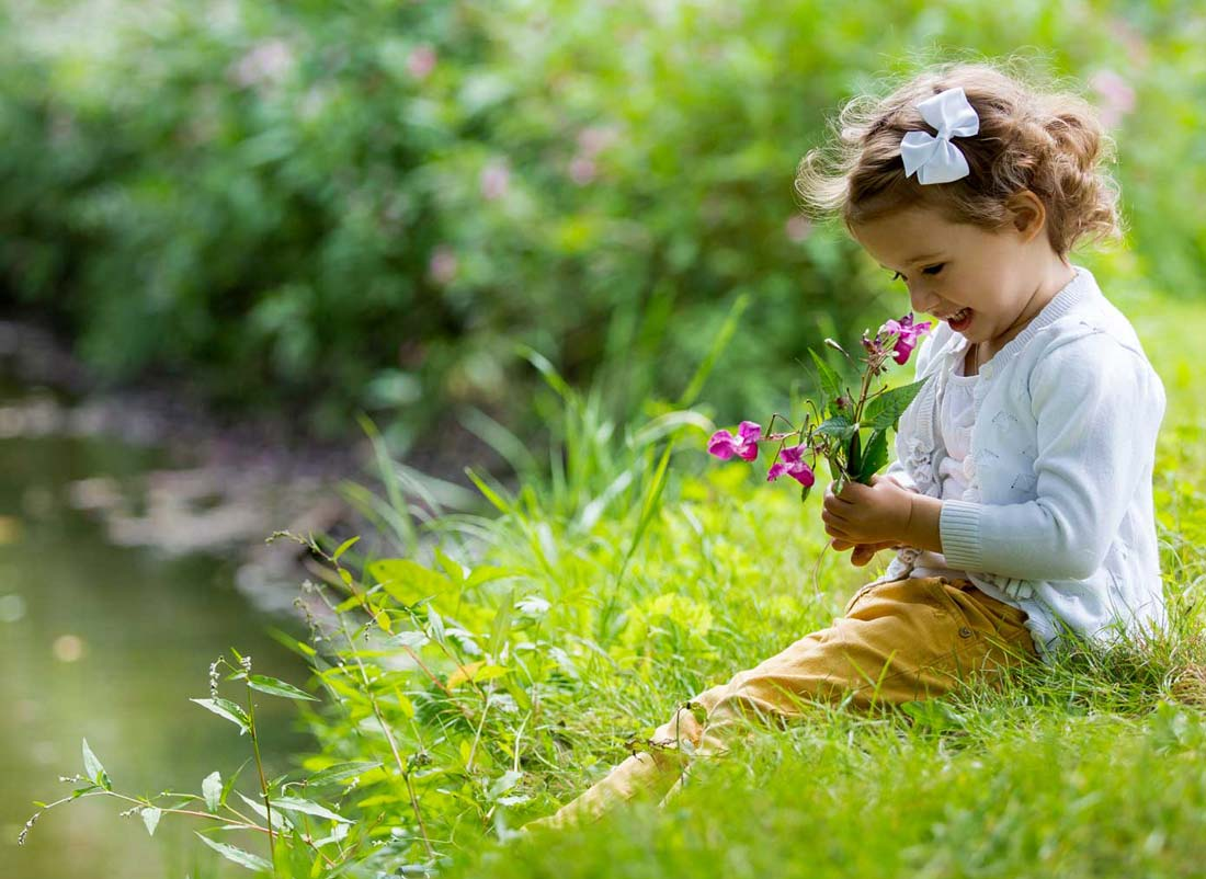 Young girl smelling flowers on the bank of a calm creek